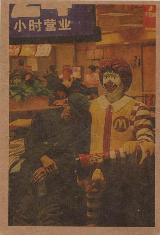 Un hombre mayor chino se inclina en una estatua de Ronald McDonald.